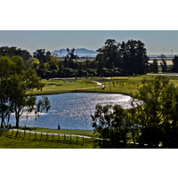A scenic overview of the Victoria Lakes Course, with golfers playing the 13th green, at River Ridge Golf Club.