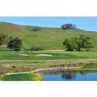 A pond protects the left side of the sixth green at San Juan Oaks Golf Club.